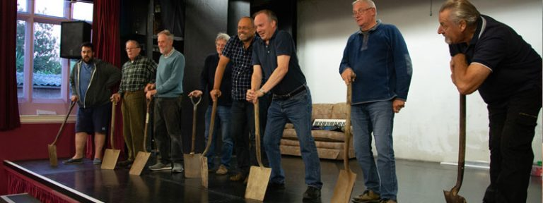 Actors on stage with spades in Lest We Forget